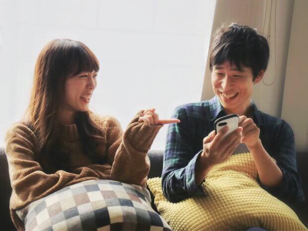 楽しそうに携帯を見るカップル