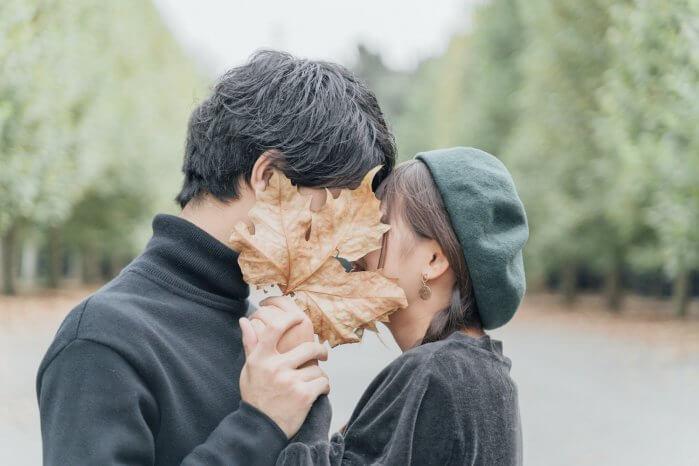 落ち葉で顔を隠すカップル
